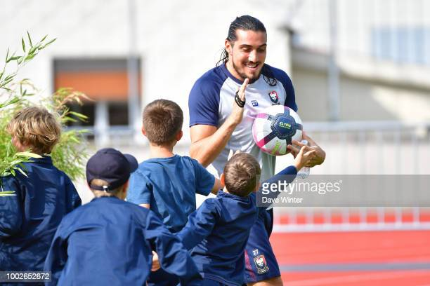 Enzo Crivelli of Caen greets the ballboys as he comes out to warm up for the preseason friendly match for the Trophee des Normands between Caen and...