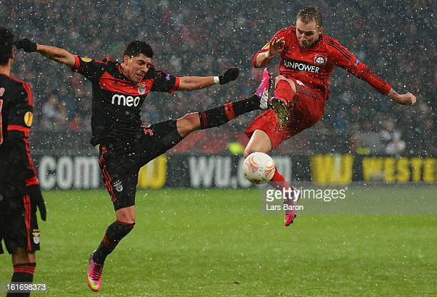 Enzo Perez of Benfica challenges Michal Kadlec of Leverkusen during the UEFA Europa League Round of 32 first leg between Bayer 04 Leverkusen and SL...