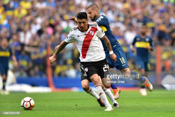 Enzo Perez of River Plate and Dario Benedetto of Boca Juniors fight for the ball during the first leg match between Boca Juniors and River Plate as...