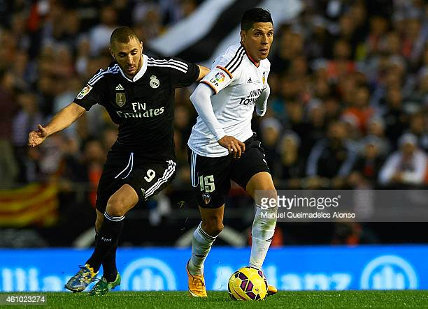 Enzo Perez of Valencia competes for the ball with Karim Benzema of Real Madrid during the La Liga match between Valencia CF and Real Madrid CF at...