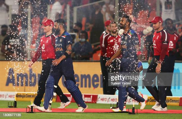 Eoin Morgan and Jos Buttler of England makes their way out alongside Virat Kohli and KL Rahul of India ahead of the 1st T20 International match...