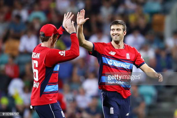 Eoin Morgan and Mark Wood of England celebrate the wicket of Marcus Stoinis of Australia during the Twenty20 International match between Australia...