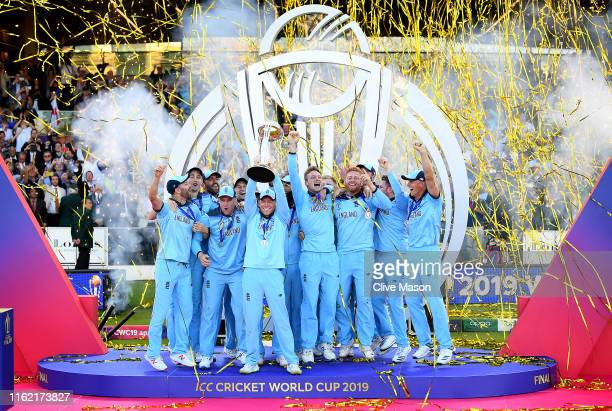 Eoin Morgan of England celebrates with his team as he lifts the Cricket World Cup trophy after the Final of the ICC Cricket World Cup 2019 between...