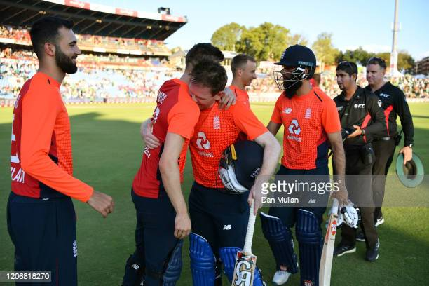 Eoin Morgan of England embraces Mark Wood of England following their victory during the Third T20 International match between South Africa and...