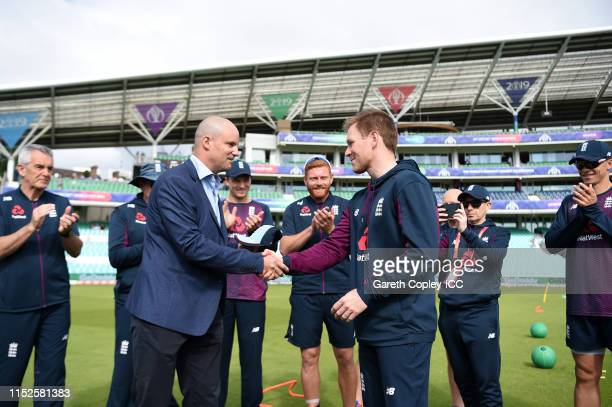 Eoin Morgan of England is presented with his 200th Cap from Former England Cricketer Andrew Strauss during the Group Stage match of the ICC Cricket...