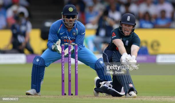 Eoin Morgan of England plays a shot watched by MS Dhoni of India during the 2nd Royal London OneDay International between England and India at Lord's...