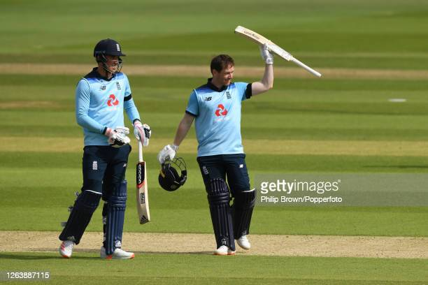 Eoin Morgan of England reaches his century as Tom Banton looks on during the third one-day international at the Ageas Bowl on August 04, 2020 in...