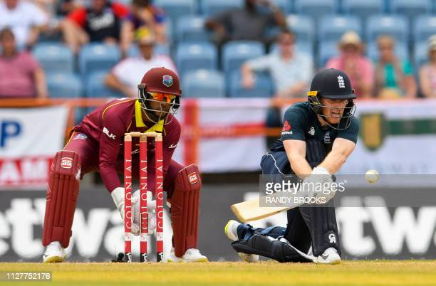 Eoin Morgan of England reverse sweeps to hit 4 as Shai Hope of West Indies watches during the 4th ODI between West Indies and England at Grenada...
