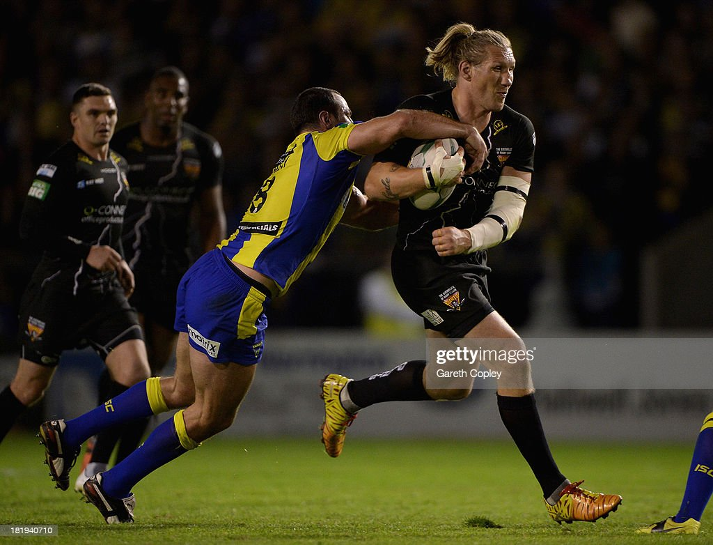 Eorl Crabtree of Huddersfield is tackled by Adrian Morley of Warrington durng the Super League Qualifying Semi Final between Warrington Wolves and Huddersfield Giants at The Halliwell Jones Stadium on September 26, 2013 in Warrington, England.