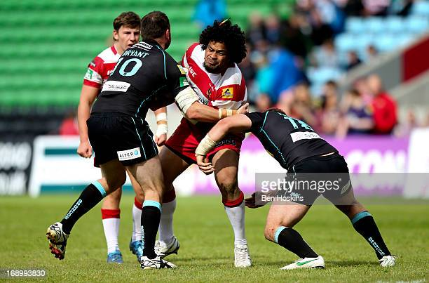 Epalahame Lauaki of Wigan is tackled by Mark Bryant and Olsi Krasniqi of London Broncos during the Super League match between London Broncos and...