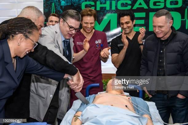 "Epatha Merkerson, Dick Wolf, Jesse Spencer, Oliver Platt, Nick Gehlfuss, Dominic Rains, and Jason Beghe, attend the ""Chicago Med"" 100th Episode Cake..."