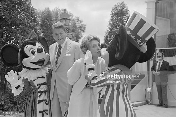 First Lady Nancy Reagan kisses Mickey Mouse as President Reagan and Minnie Mouse watch The Reagans were at EPCOT Center 5/27 to review 20 bands...