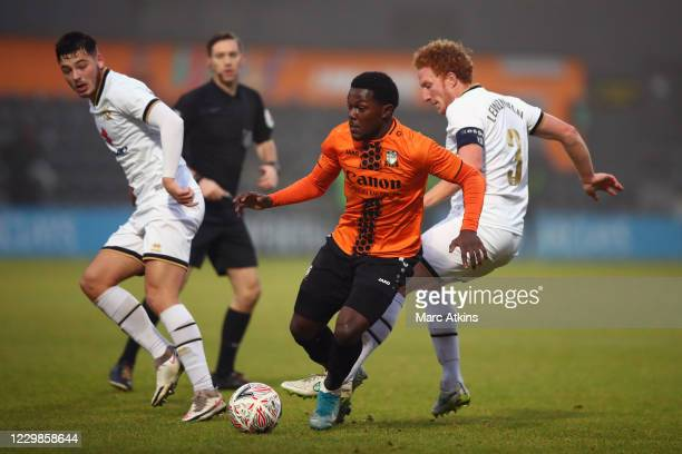 Ephron Mason-Clark of Barnet in action with Dean Lewington and Stephen Walker of MK Dons during the Emirates FA Cup Second Round match between Barnet...