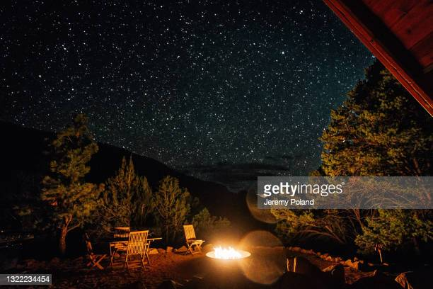 epic, starry sky from a modern a-frame tiny home at night with millions of bright stars and a gas fire pit on a clear night in the summer - national forest stock pictures, royalty-free photos & images