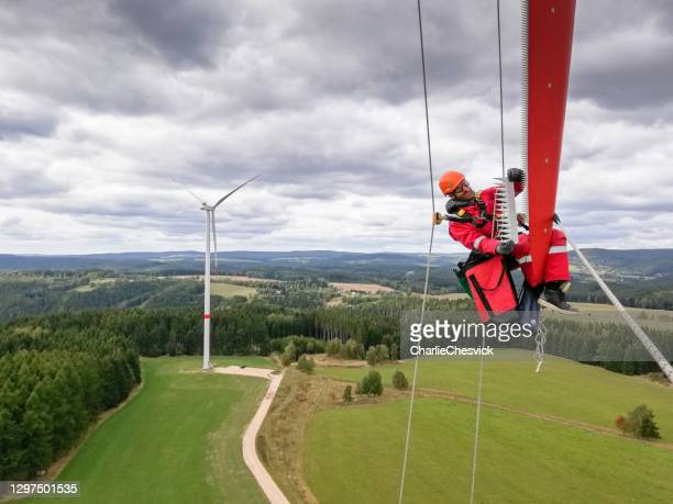 epic view on industrial climber,  rope access technician working on tip of the wind turbine blade fasten serrations on trailing edge and with windfarm is behind him, dramatic sky - tower stock pictures, royalty-free photos & images
