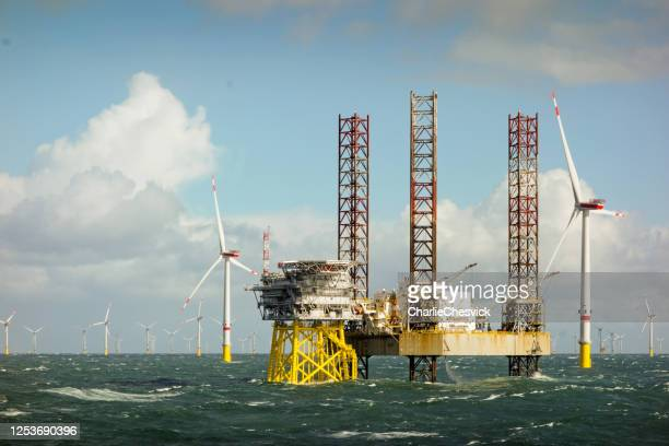 epic view on large offshore 8mw wind turbines, wind farm on the horizont in north sea with jack up boat and offshore platform in wavy sea - north sea stock pictures, royalty-free photos & images