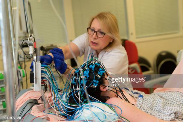 Epileptology unit Nice France Carrying out an emergency EEG in the intensive care service on a patient who was hospitalized following a convulsive...