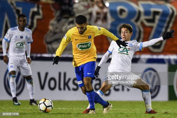 Epinal's French forward Mohamed Labhiri vies with Olympique de Marseille's French midfielder Maxime Lopez during the French Cup football match...