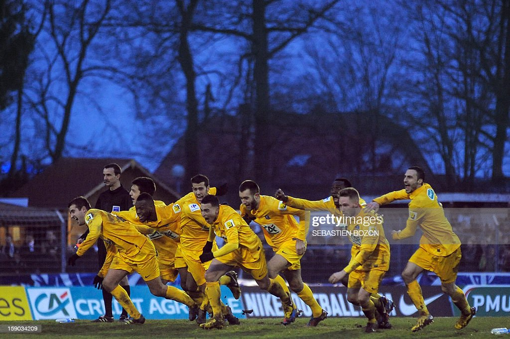Epinal's players celebrate after beating Lyon during their French cup football match Epinal (SAS) vs Lyon (OL) at the Colombiere Stadium in Epinal, on January 6, 2013.