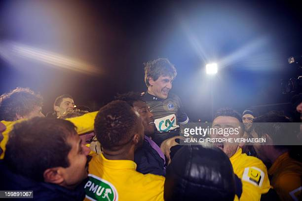Epinal's players celebrate after defeating Nantes during the French Cup football match between Epinal and Nantes at La Colombiere stadium on January...