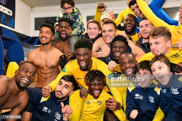 TOPSHOT Epinal's players celebrate their team's win at the end of the French Cup roundof16 football match between Epinal and Lille at the stade de la...