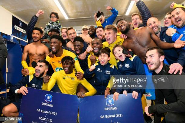 Epinal's players celebrate their team's win at the end of the French Cup roundof16 football match between Epinal and Lille at the stade de la...