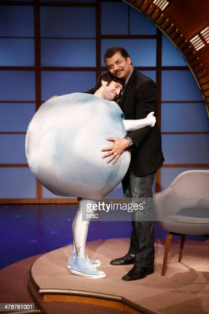Episode 0015 -- Pictured: Seth Reiss as Pluto hugs astrophysicist Neil deGrasse Tyson on March 14, 2014 --