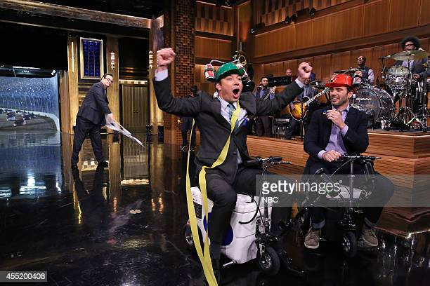 Announcer Steve Higgins looks on as host Jimmy Fallon and race car driver Jimmie Johnson have a 'coolerscooter' race on September 10 2014