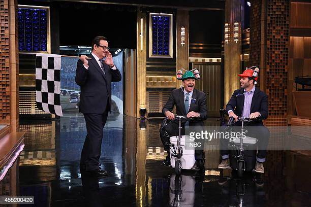 Announcer Steve Higgins looks on as host Jimmy Fallon and race car driver Jimmie Johnson have a coolerscooter race on September 10 2014