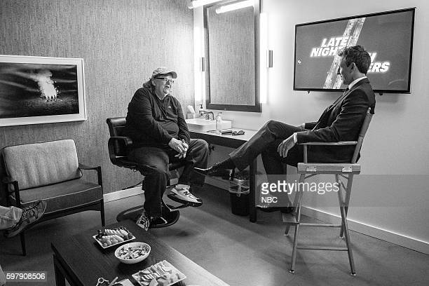 MEYERS Episode 410 Pictured Director Michael Moore talks with host Seth Meyers backstage on August 29 2016