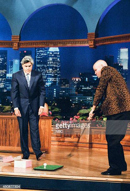Host Jay Leno looks on as golfer John Daly prepares to swing on August 8 1995