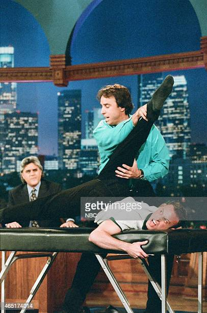 Host Jay Leno and actor Kevin Nealon during Kevin's Massage Contortionist sketch on June 4 1996