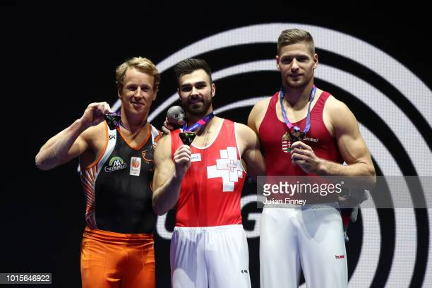 Epke Zonderland of the Netherlands Oliver Hegi of Switzerland and Dávid Vecsernyés of Hungary pose for a photo with their medals for Horizontal Bar...