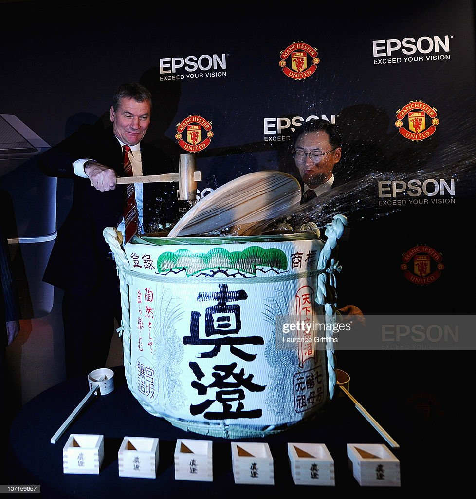 Epson Global President Mr Minoru Usui breaks a sake barrell with Manchester United Chief Executive David Gill during a Press Conference as Manchester United launch a new sponsorship deal with Epson at Old Trafford on November 26, 2010 in Manchester, England.