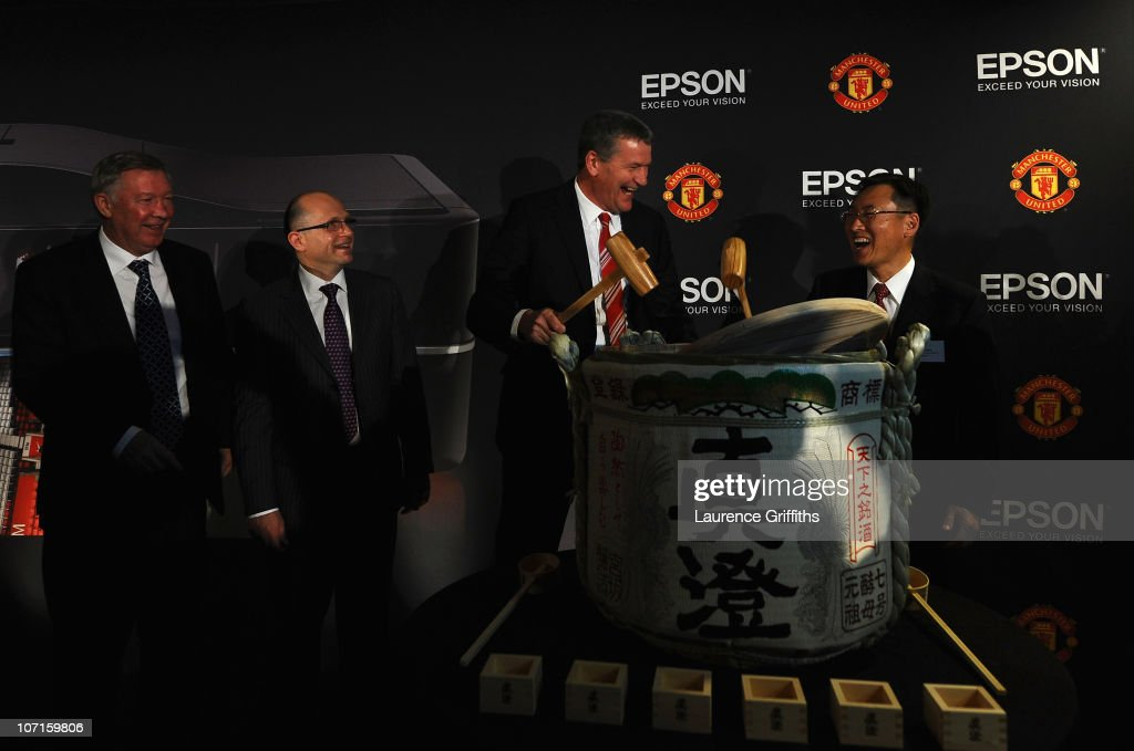 Epson Global President Mr Minoru Usui breaks a sake barrell with Manchester United Chief Executive David Gill watched by Sir Alex Ferguson during a Press Conference as Manchester United launch a new sponsorship deal with Epson at Old Trafford on November 26, 2010 in Manchester, England.