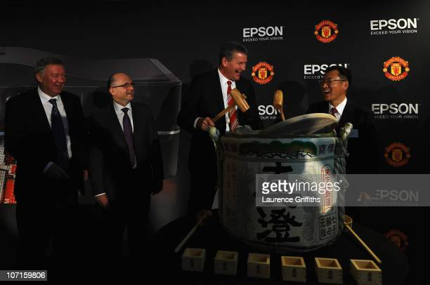Epson Global President Mr Minoru Usui breaks a sake barrell with Manchester United Chief Executive David Gill watched by Sir Alex Ferguson during a...