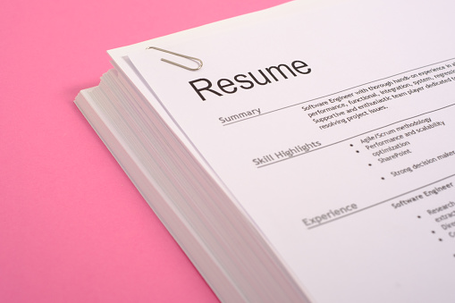 Equal opportunities career concept.Pile of cv isolated on pink background 944655566