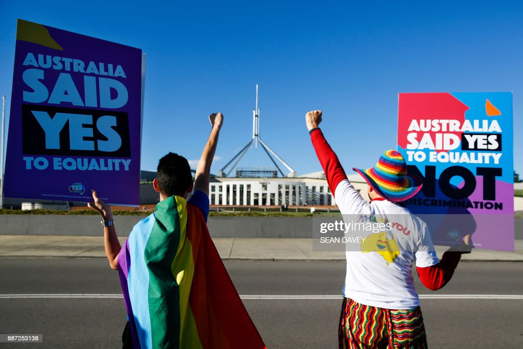 Equality ambassadors and volunteers from the Equality Campaign celebrate as they gather in front of Parliament House in Canberra on December 7, 2017, ahead of the parliamentary vote on Same Sex Marriage, which will take place later today in the House of Representatives. /