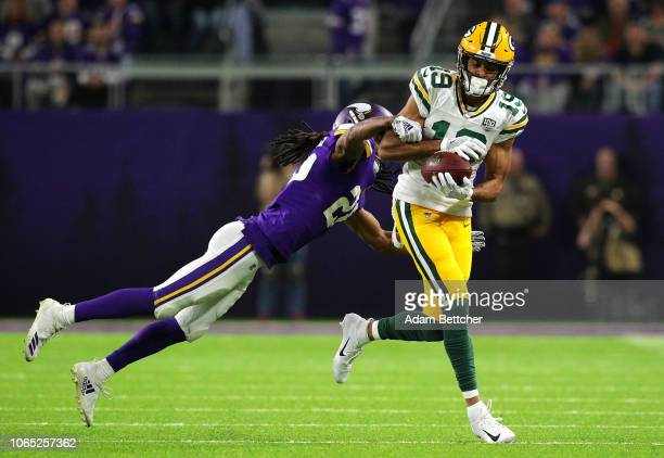Equanimeous St. Brown of the Green Bay Packers catches the ball as he is hit by Trae Waynes of the Minnesota Vikings in the second quarter of the...