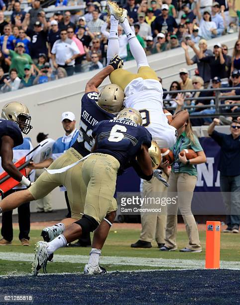 Equanimeous St Brown of the Notre Dame Fighting Irish dives for the goal while be tackled by Sean Williams and Hudson Sullivan of the Navy Midshipmen...