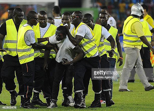 Equatorial Guinea fan is carried by security after invading the pitch during the 2015 African Cup of Nations semifinal football match between...