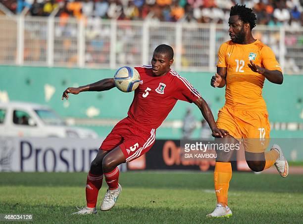 Equatorial Guinea's Diosdado Mbele controls the ball as Ivory Coast's Bony Wilfried looks on during the friendly football match Ivory Coast againt...