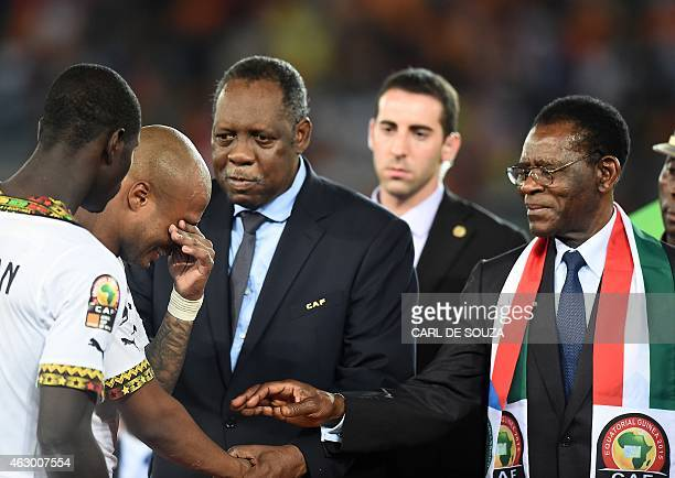 Equatorial Guinea's President Teodoro Obiang Nguema Mbasogo and Confederation of African Football president Issa Hayatou try to console Ghana's...