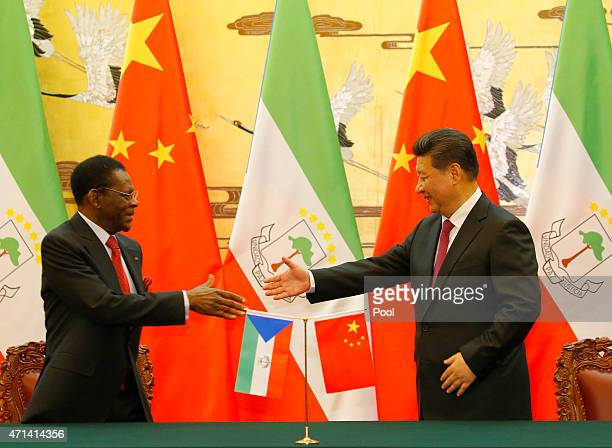 APRIl 28: Equatorial Guinea's President Teodoro Obiang Nguema Mbasogo shakes hands with Chinese President Xi Jinping during a signing ceremony at the...