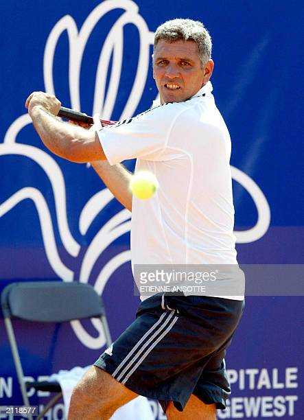 Equatorian former professionnal player Andres Gomez hits a backhand to French Cedric Pioline during their first round match of the Iris Champions...