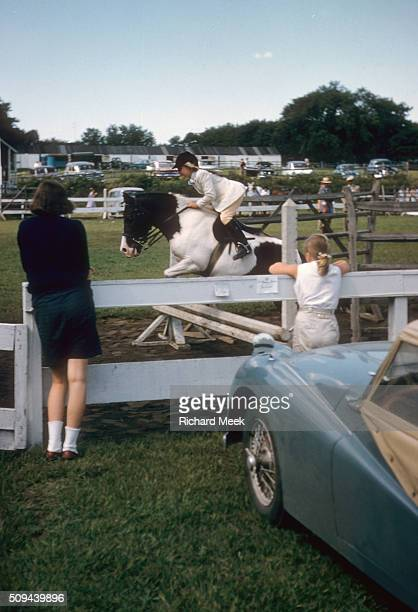 Junior Horse Show Abbie Arms in action riding pony Patches over working hunter pony sweepstake course at Fairfield County Hunt Club Westport CT...