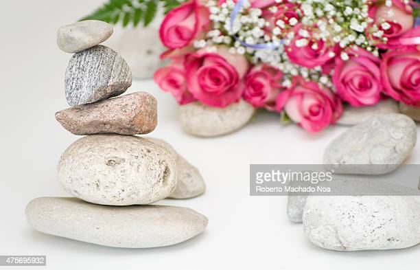Equilibrium concept Beautiful composition of the pyramid with stones and blurred bouquet of roses in the background