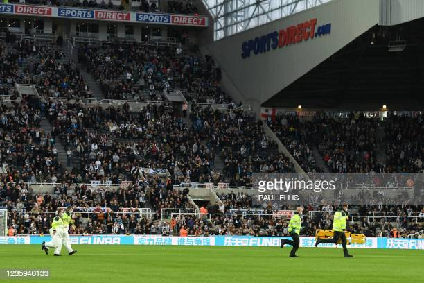 Equipment is taken across the pitch after a medical emergency in the crowd stops play shortly before half time during the English Premier League...