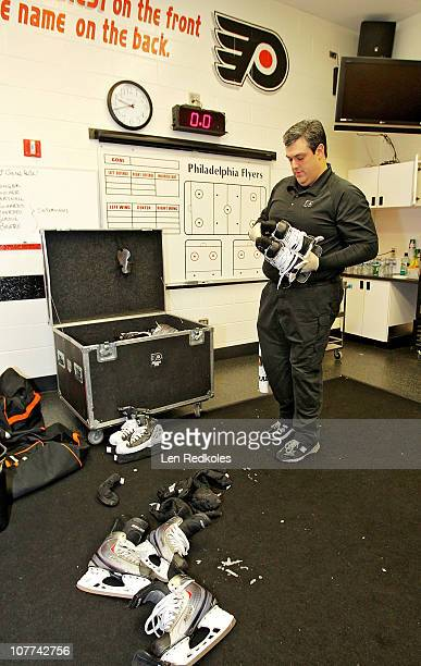Equipment Manager Harry Bricker of the Philadelphia Flyers attends to the players skates following a 32 win over the Pittsburgh Penguins on December...