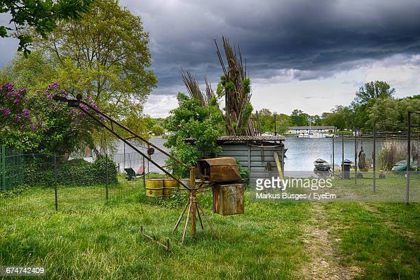 Equipment On Grassy Field By River Against Cloudy Sky